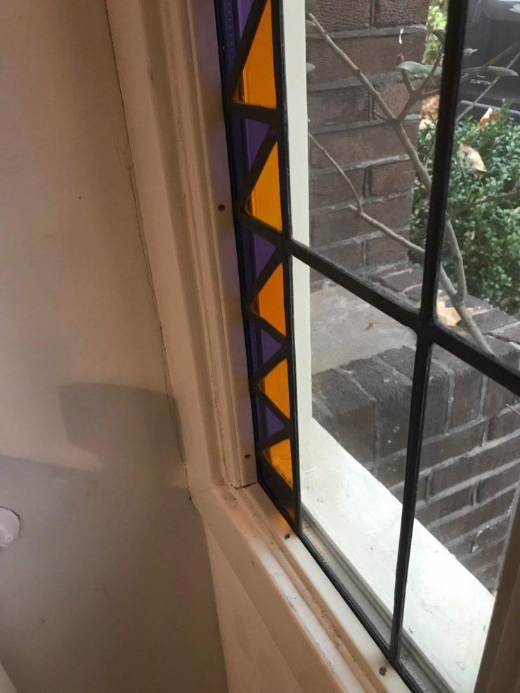 Glas in lood met getoogde vorm hersteld en terug geplaatst.